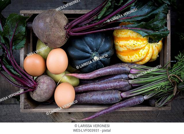 Wooden box of different organic vegetables