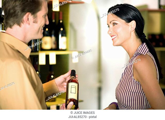 Couple looking at wine in liquor shop