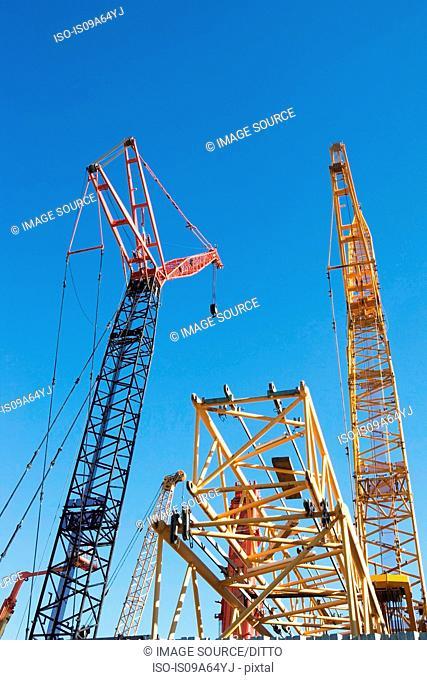 Colorful cranes against blue sky