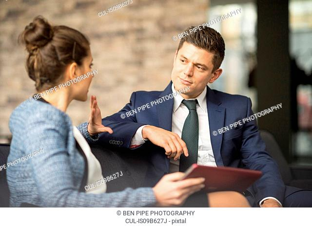 Businessman and woman meeting on office sofa