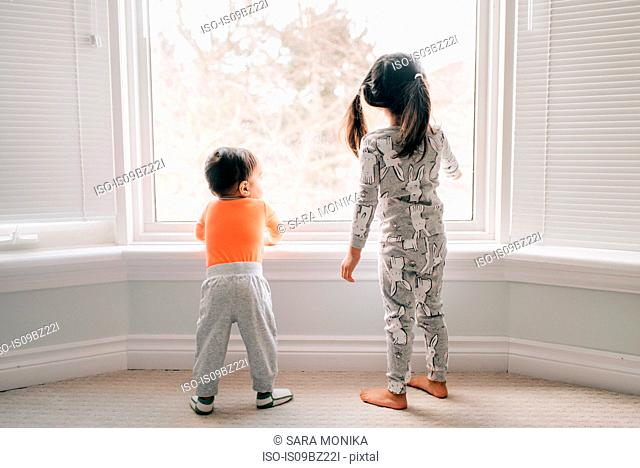 Girl and baby brother looking through living room window, rear view