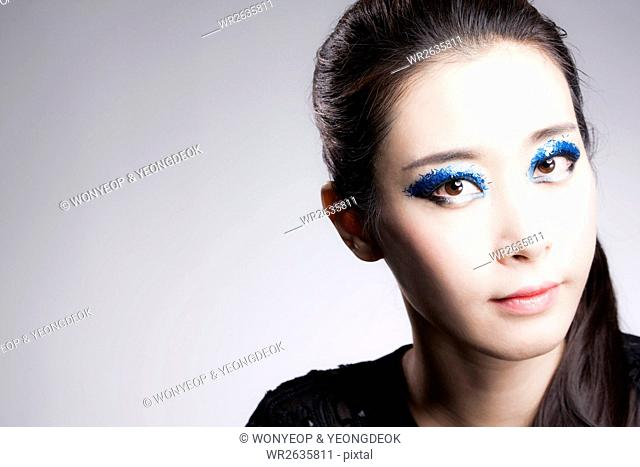 Portrait of young Korean woman in blue eye shadow