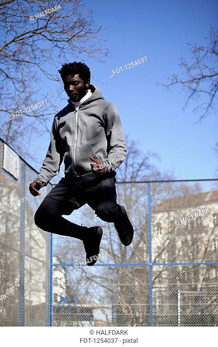 A serious young man jumping high in the air, Berlin, Germany