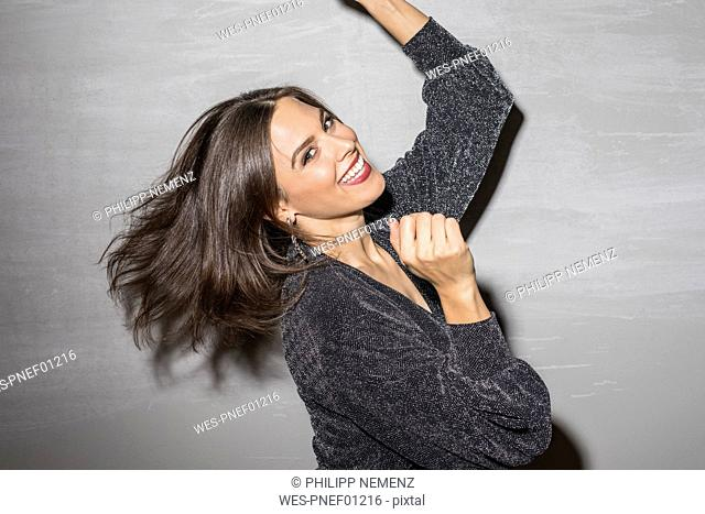 Portrait of laughing young woman dancing at party