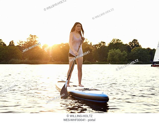 Germany, Hamburg, Young woman on paddleboard enjoying summer