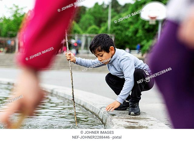 Boy playing in pond