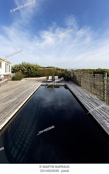 Dark luxury swimming pool under sunny blue sky