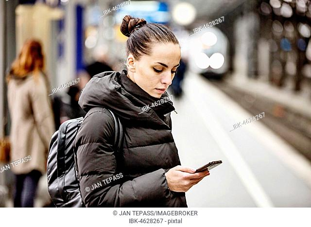 Young woman on a platform in the main station looks at her smartphone, Cologne, North Rhine-Westphalia, Germany