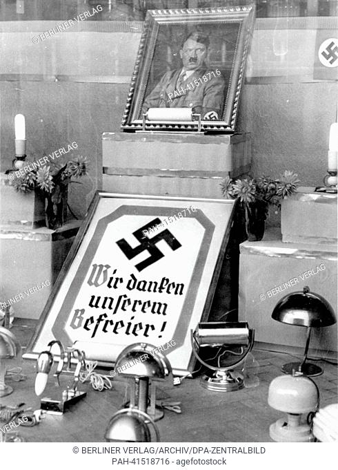 "The image from the Nazi Propaganda! shows a portrait of Adolf HItler and the writing """"We thank our liberator"""" below a swastika in the display window of a..."