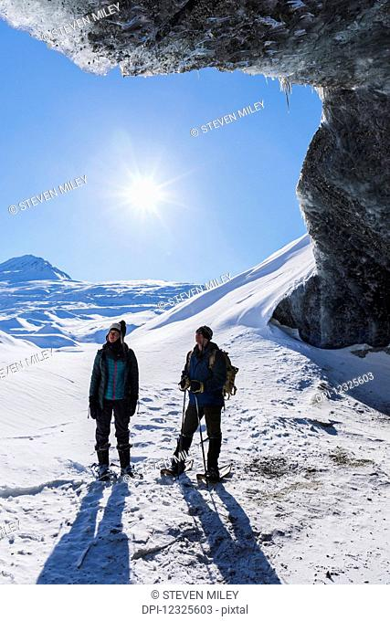 A couple snowshoeing and standing beneath the entrance to an ice cave on a sunny winter day at Canwell Glacier in the Alaska Range; Alaska