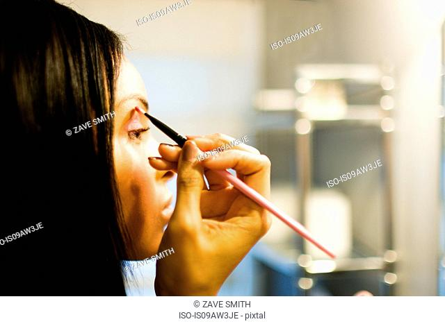 Close up of young woman putting on eye shadow with brush