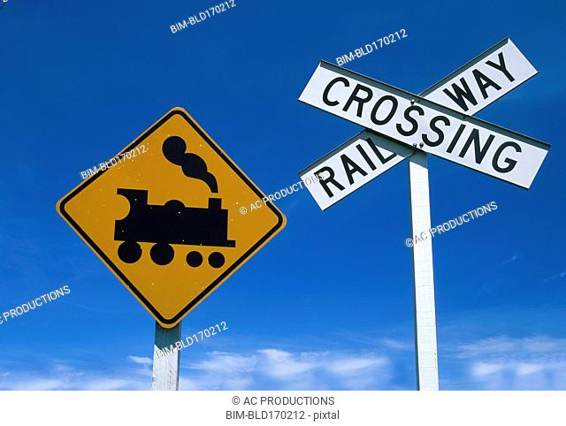 Low angle view of railway crossing signs