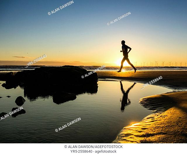 Jogger on beach at sunrise. Seaton Carew, England, United Kingdom