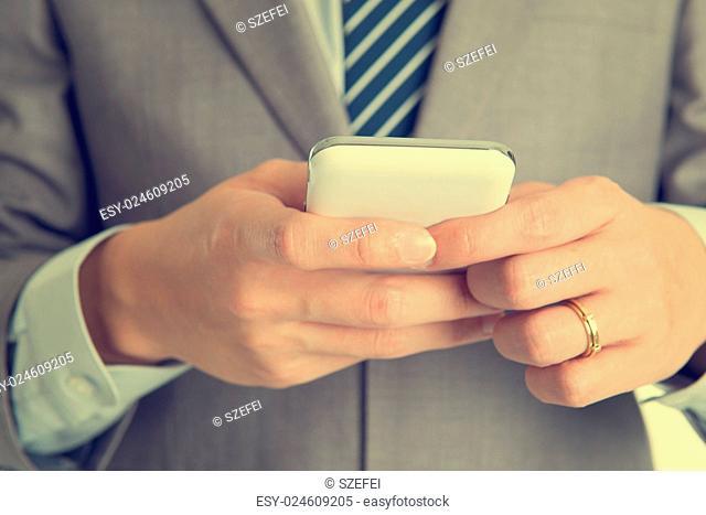 Close-up businessman hand using smart phone in retro tone