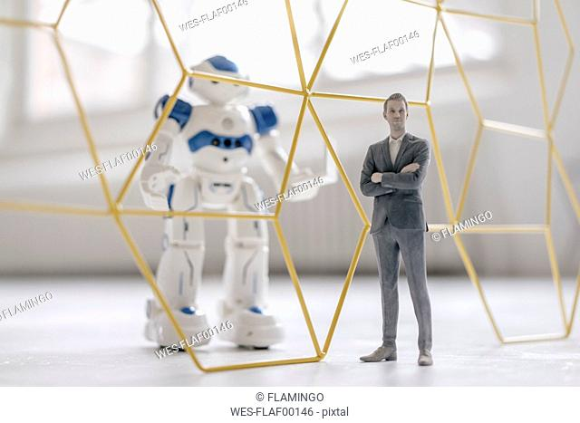 Miniature businessman figurine standing in front of robot with laptop seperated by structure