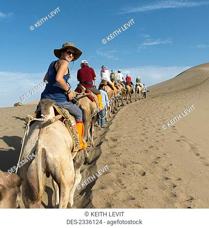 Tourists ride in a row on camels; Jiuquan, Gansu, China