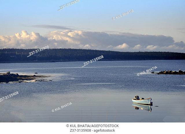A boat moored in a calm sea in a cove of the Atlantic Ocean, Nova Scotia, Canada