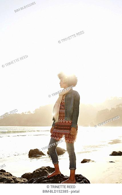Mixed race woman standing on boulder on beach
