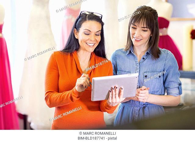 Hispanic entrepreneurs using digital tablet in bridal shop