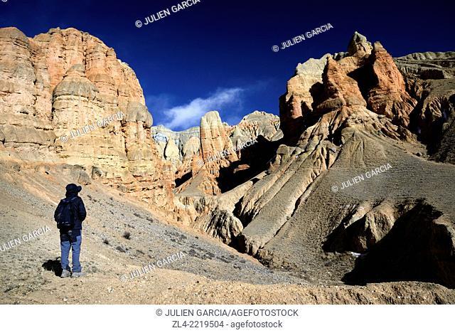 Trekker near red and ochre rock formations in a valley near Dhakmar village. Nepal, Gandaki, Upper Mustang (near the border with Tibet)