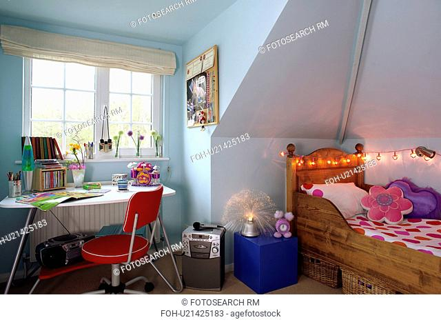 Teenager's pastel blue attic bedroom with novelty fairy lights above wooden bed