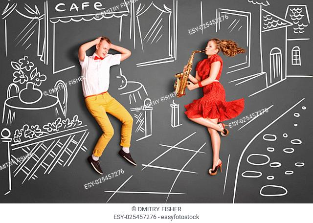 Love story concept of a romantic couple against chalk drawings background. Woman playing the sax on the street for her lover