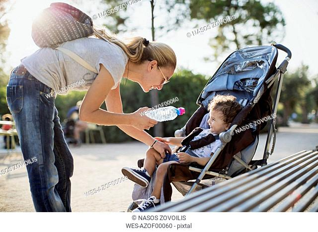 Mother giving water bottle to his son, sitting in pram