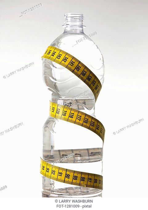 A plastic water bottle full of water and wrapped with a tape measure