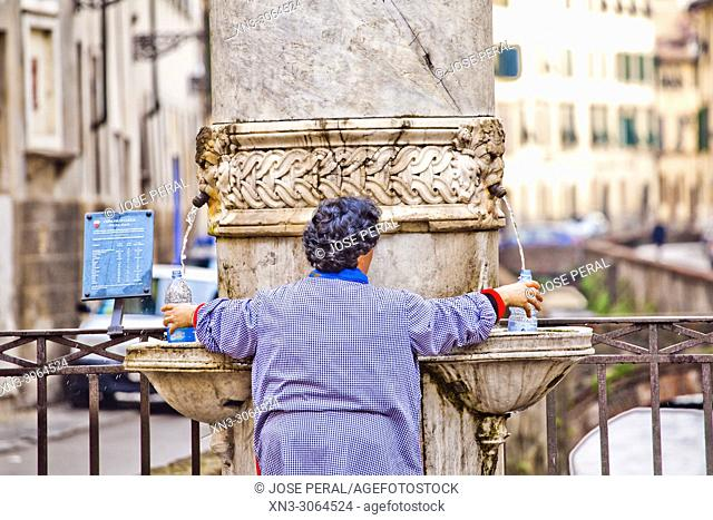 Funny scene of woman taking water, drinking fountain over Canal, Via del Fosso street, Lucca, Tuscany, Italy, Europe