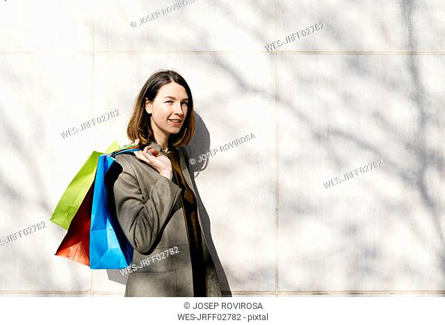 Portrait of smiling woman with shopping bags standing at a wall
