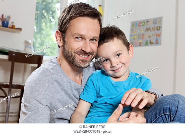 Germany, Berlin, Father and son at home, smiling, portrait
