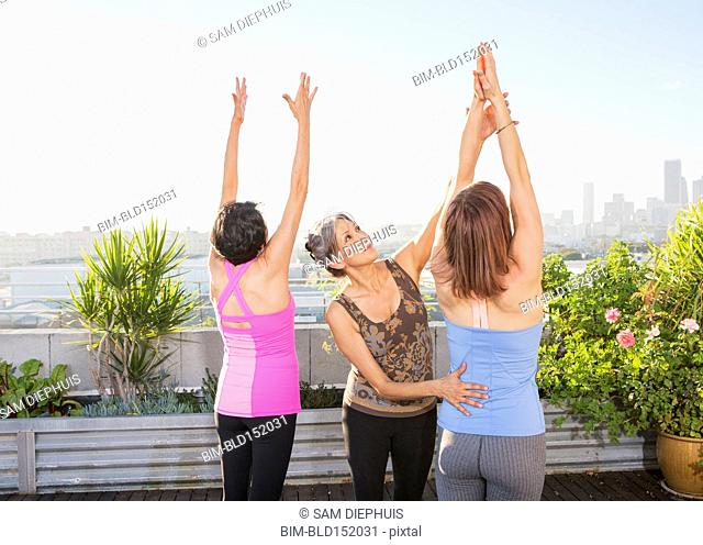 Teacher helping yoga students in class on urban rooftop