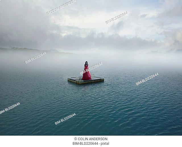 Middle Eastern woman floating on dock in remote lake