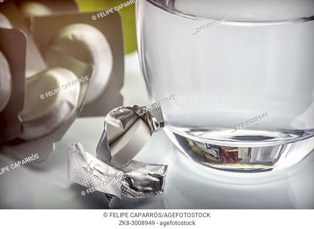 Glass of water next to an effervescent pill, conceptual image