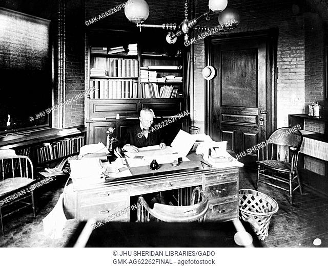 William Julian Albert Bliss, faculty member of the Johns Hopkins University and lecturer on electricity, Candid photograph, Sitting in office, Chest up