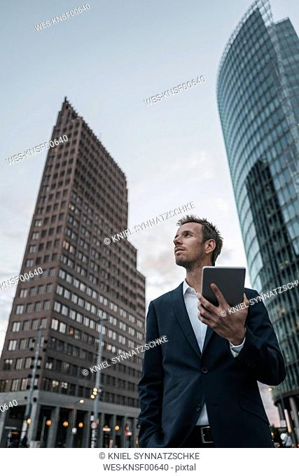Germany, Berlin, businessman with tablet standing at Potsdamer Platz