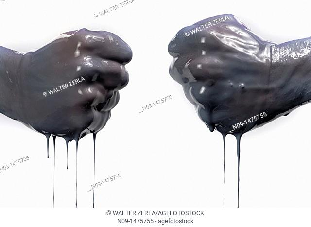 two fists with dark liquid