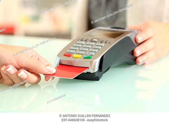 Close up of a seller hands using a dataphone to charge with credit card on a desk in a store