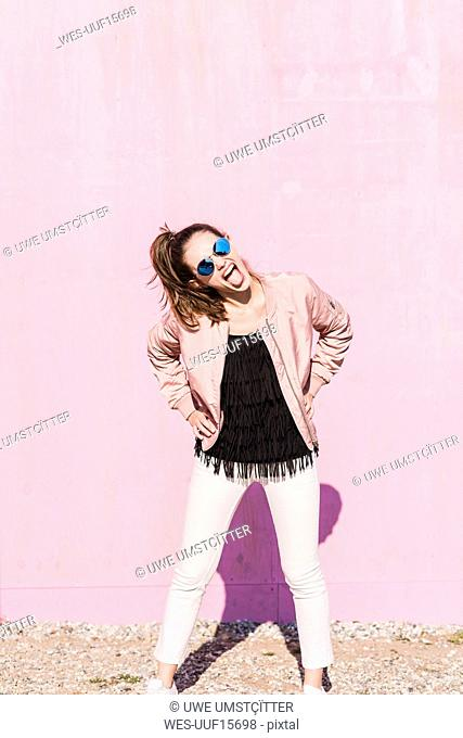 Exuberant young woman screaming in front of pink wall