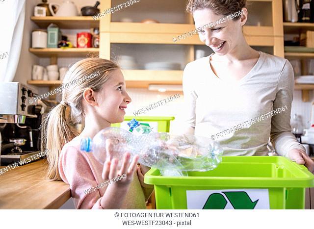 Mother and daughter at home separating waste