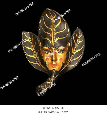Sinister venetian mask with gold face and leaves on black background