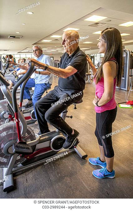 Accompanied by his Asian American instructor, a healthy 92-year-old man works out on an exercise bicycle in the gymnasium of a senior center in Huntington Beach