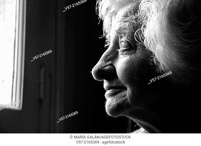 Profile portrait of an elderly woman smiling. Black and White
