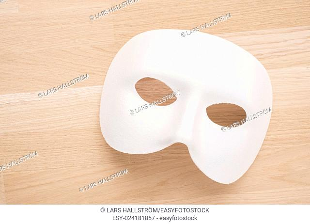 White mask in close up on wooden table. Still life of theatre, carnival or masquerade. Can also be a concept for hiding behind a disguise