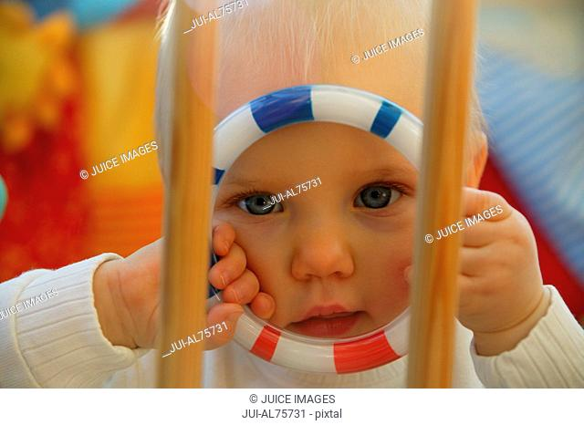 View of baby girl holding a toy in a crib
