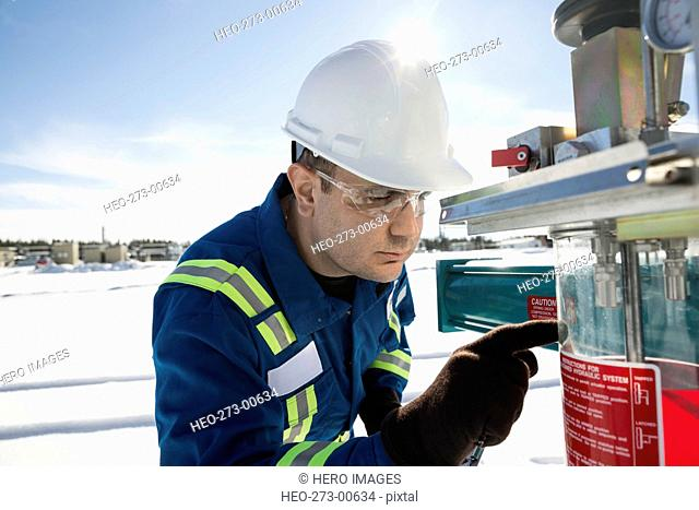 Male worker examining equipment at gas plant
