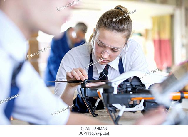 High school student assembling robot in shop class