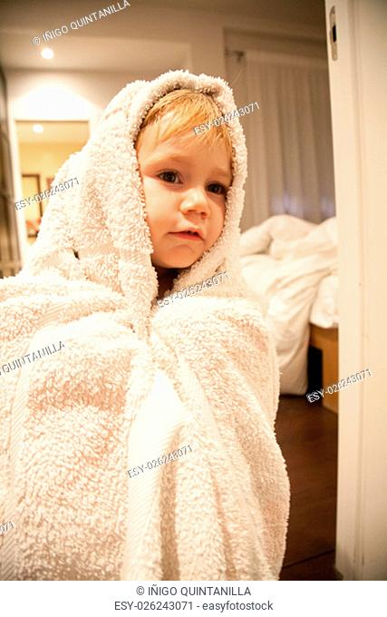 blonde caucasian baby two years old age chubby face wrapped in white bath towel looking indoor bedroom home