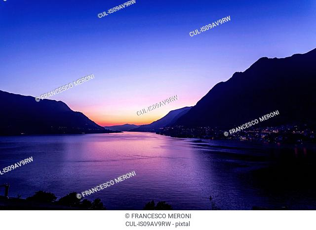 Lake with silhouetted mountains at sunset, Pognana Lario, Lombardy, Italy