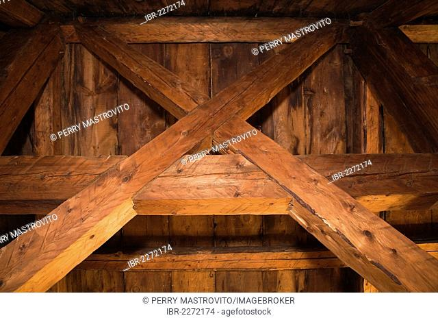 Exposed beams, rafters and roof boards in the attic of an old Canadiana cottage-style residential fieldstone home, circa 1755, Montreal, Quebec, Canada